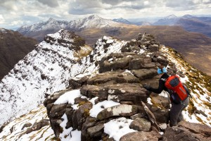 A hiker climbing over the three horns on Ben Alligin Ridge in the Torridon Mountains, Scottish Highlands.